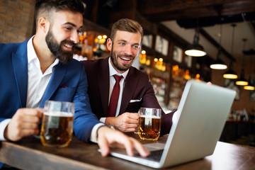 Business people drink beer after work. Businessmen enjoy a beer.