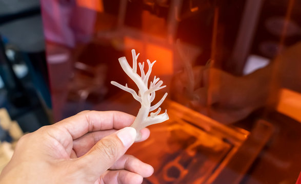 hand with object in shape of medically accurate a human blood vessel printed on 3d printer