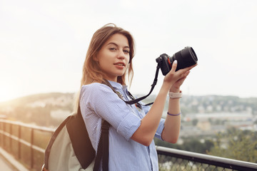 Female photographer came to Europe. Lady walking on street and making photos of sights using professional camera. Cute girl wearing backpack behind