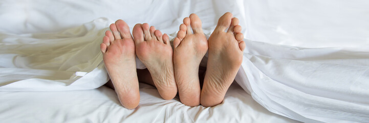 Close up of four feet of a couple in a bed, panoramic web banner