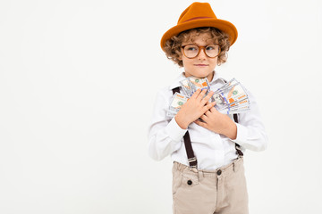 Beautiful boy with curly hair in white shirt, brown hat, glasses with black suspenders holds money isolated on white background