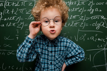 smart kid touching glasses and standing with hand on hip near chalkboard
