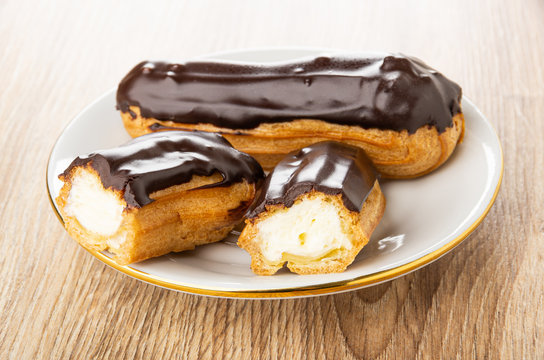 Eclair with chocolate glaze, halves of eclair in saucer on wooden plate