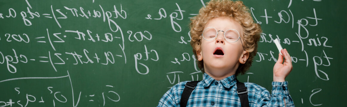 panoramic shot of curly kid in glasses sneezing near chalkboard with mathematical formulas