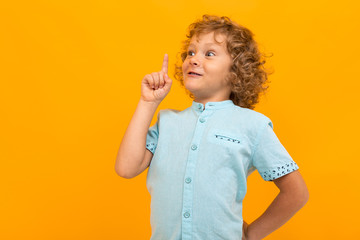 Little boy with curly hair in blue shirt and shorts have a great idea isolated on yellow background