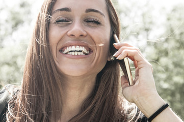 Happy carefree customer talking on phone and laughing. Closeup of woman with closed eyes speaking on cellphone and laughing. Communication and positive emotion concept