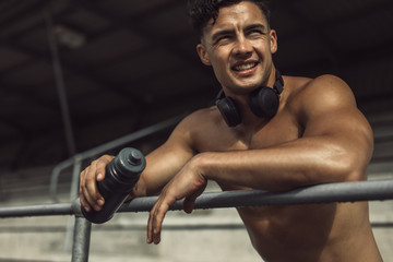 Muscular man with water bottle taking rest after workout