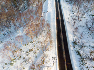 Oblique view from height of a empty road cutting through snow covered ground with a sped limit sign of 50 km per hour