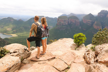 hiking couple standing at edge of mountain Wall mural