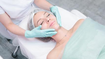 Fototapeta The female dermatologist do face massaged to beautiful girl cosmetology cabinet or beauty clinic.