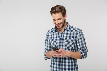 Portrait of happy young man smiling and using cellphone