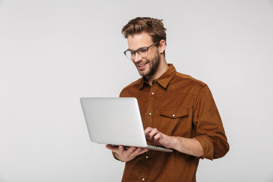 Portrait of cheerful young man using laptop and smiling