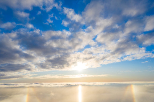 Aerial view White clouds in blue sky with solar halo. Top view. View from drone. Aerial bird's eye view. Aerial top view cloudscape. Texture of clouds. View from above. Sunrise or sunset over clouds