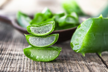 Fresh aloe vera leaves and slices of aloe vera on a wooden background.