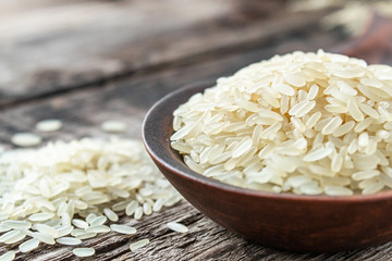 A bowl of white rice against the background of old boards near sprinkled rice. Jasmine rice for cooking.