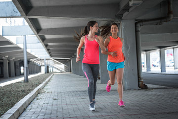 Poster Jogging Two female runners jogging around the city road overpass.Urban workout concept.