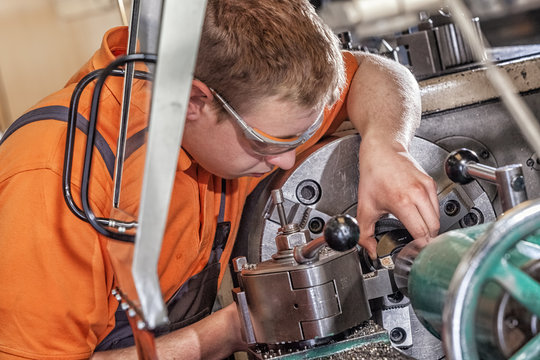 A skilled worker in the metalworking industry working on a lathe