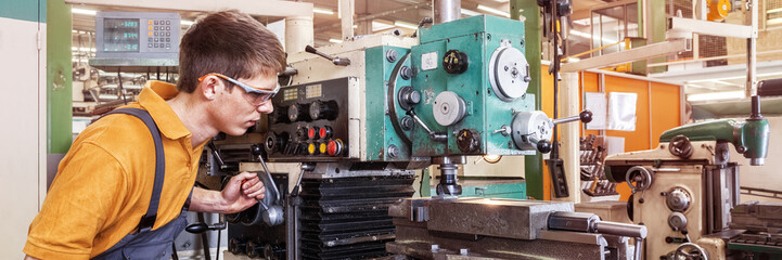A trainee in the metalworking industry works on a milling machine