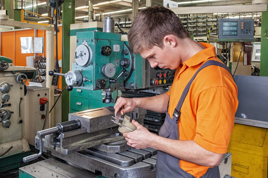 A trainee in the metalworking industry checks a workpiece using a caliper