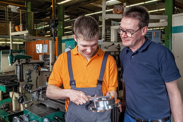 A trainee in the metalworking industry and the instructor check a workpiece using a caliper
