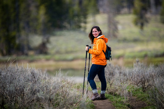 Self care exercise outdoors Young brunette beautiful attractive woman hiking in parka with walking sticks near forest in wilderness while camping