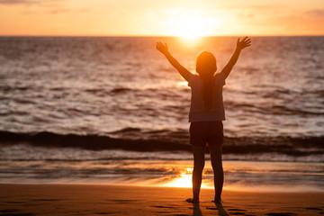 Child enjoying the freedom of sunset and sea