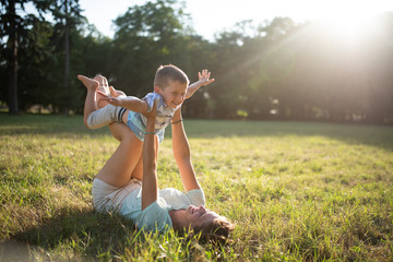 Kid taking feel of airplane, playing with mother.