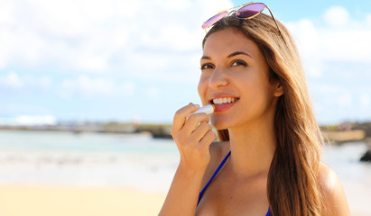 Smiling young woman applying sun protection on her lip on the beach. Attractive young woman putting lip balm on lips.
