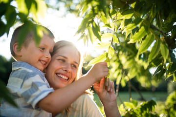 Smiling mom teaching nature love to son