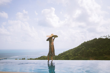 Papiers peints Budapest A beautiful girl in a swimsuit, a hat and a robe developing in the wind stands in a villa with a pool and beautiful views of the jungle and the sea. Thailand, Samui
