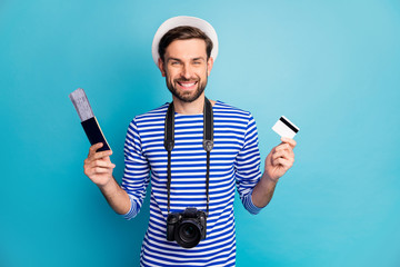 Photo of attractive guy photographer hold professional digital camera traveler buy tickets with help of credit card wear striped sailor shirt vest cap isolated blue color background