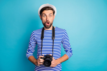 Photo of shocked guy photographer paparazzi hold professional lens camera see celebrity abroad street make pictures wear striped sailor shirt vest cap isolated blue color background