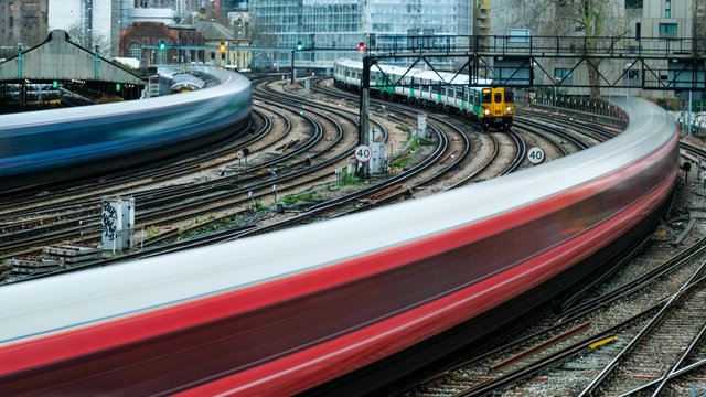 Motion blurred trains arriving on to railway station