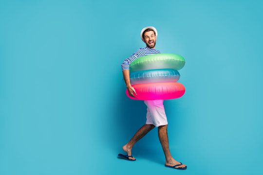 Full length profile photo of funky guy tourist walking seaside inside three colorful rubber lifebuoys swimmer wear striped sailor shirt cap shorts flip flops isolated blue color background