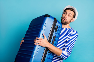 Photo of handsome guy traveler hold big suitcase plane flight weight allowance too heavy bag feel back pain wear striped sailor shirt vest panama isolated blue color background