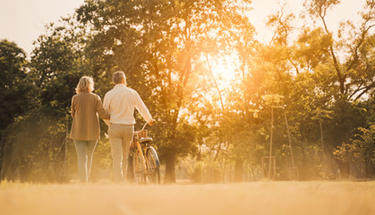 Beautiful Senior couple walking their bike along happily talking in park.Elderly man and old woman with bicycles outside in spring nature.Happy senior couple  holding hands while walking at sunset.