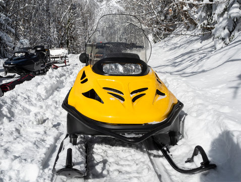 Front view of yellow and black snowmobiles on snow at winter sunny day