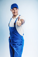 Portrait of young worker man wearing blue uniform. Showing thumb up. Movement cool. Isolated on grey background with copy space. Human face expression, emotion. Business concept.