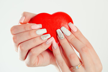 Love for manicure art concept. Beauty hands holding red heart shaped jewelry box. Stylish pastel Color pink coral white Nails isolated white background. Classic wedding bride nails design Nail Polish.