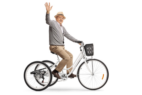 Senior man riding a tricycle and waving at the camera