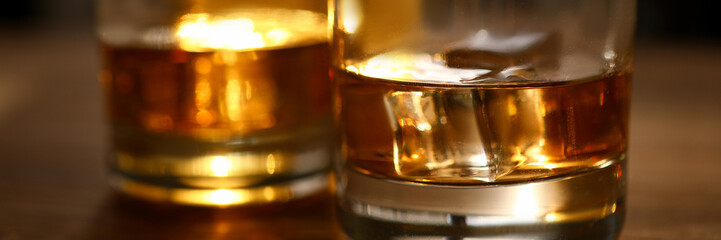 Focus on glasses of whisky or bourbon with ice-cubes. Glassful of delicious beverages on wooden table. Celebration and relax concept. Blurred background