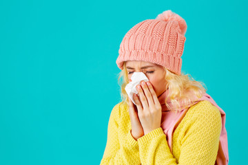 Cold and flu season- portrait of a woman in hat and scarf blowing her nose