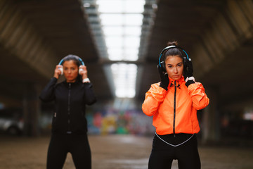 Two young fitness woman with headphones ready for jogging under overpasses during a cold day