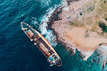 Fotobehang Schipbreuk Top view of a ship stranded near the shore, drone shot.