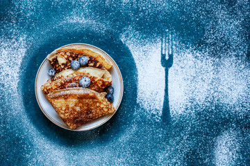 Delicious homemade pancakes with blueberries and powdered sugar  on classic blue background. Top view, close up