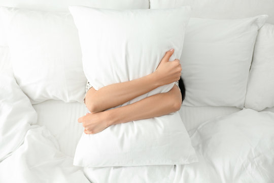 Young woman with pillow in bed, top view. Lazy morning