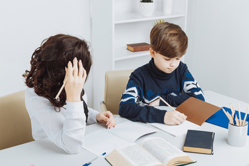 Picture of the boy doing his homework and his mother helps him