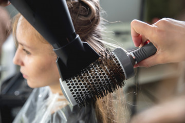 Close up of hairdressers hands drying long blond hair with blow dryer and round brush Fototapete