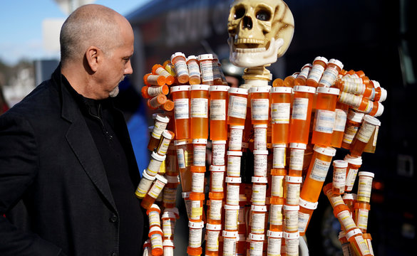 Frank Huntley looks at his sculpture made out of the opioid pill bottles he got when addicted, set up outside Democratic presidential candidate and former Vice President Joe Biden's campaign event in Somersworth