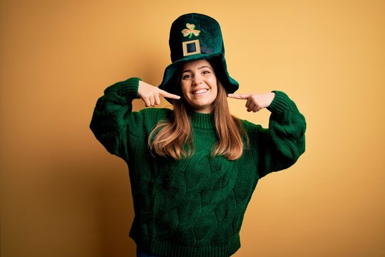 Young beautiful brunette woman wearing green hat on st patricks day celebration smiling cheerful showing and pointing with fingers teeth and mouth. Dental health concept.